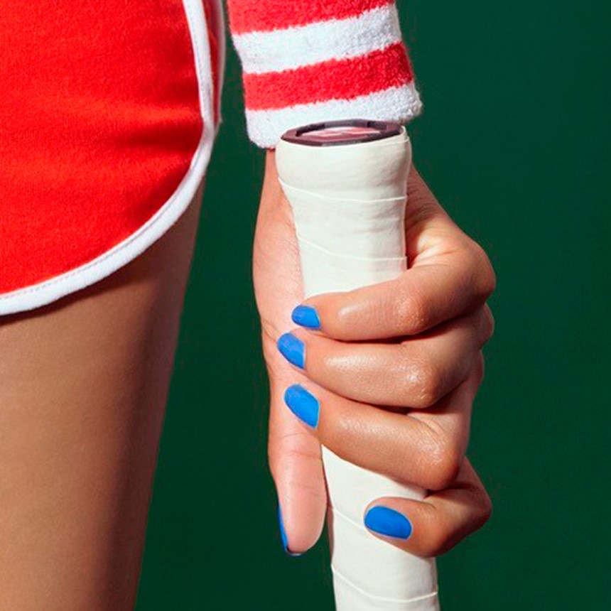 zoom on a hand wearing blue nailmatic nail polish holding a tennis racket - red shorts detail