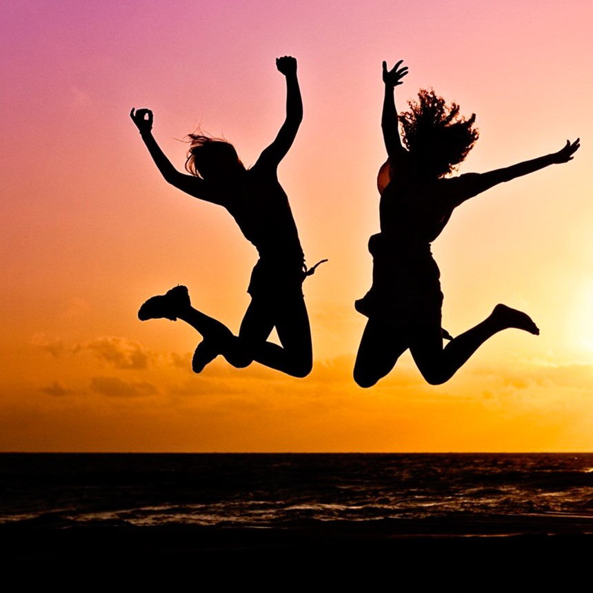girls who jump in the air in front of a sunset